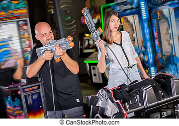 Young couple posing with a toy shotgun on target in room