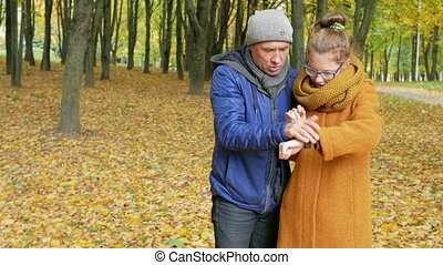 Daughter teenager teaches her father to work with the smart watch in the autumn park. Dad listens carefully and repeats the daughter of her touch display