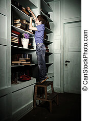 Freckled red-haired little boy searching book on bookcase in...