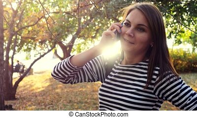 Happy young woman on smart phone in autumn park. 3840x2160....