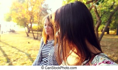 Beautiful girls walking in autumn park in sunny day on the...