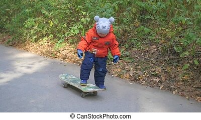 a small child learns to ride a skateboard in the Park