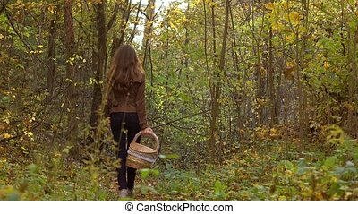 Girl walking in autumn forest holding a basket. 4K steadicam video