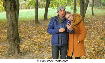 Daughter and father talking on the phone in the autumn park on the video. Dad smiles and laughs with her daughter a teenager. happy family concept