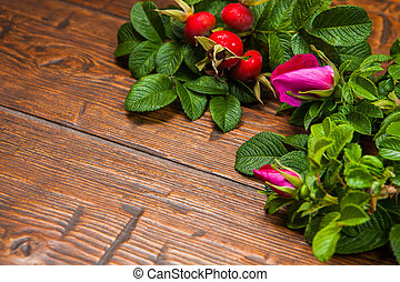 Ripe rosehips with pink rose on a wooden table