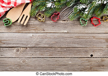 Christmas cooking utensils and snow tree on wooden table....