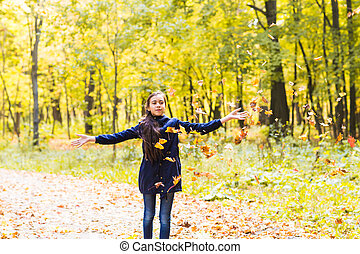 attractive teen girl throwing leaves in the air