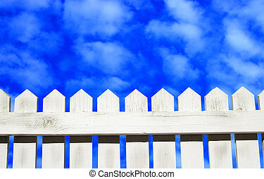 White picket fence and blue sky