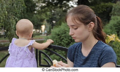 A young nanny and a baby girl eating a baguette. The nanny...