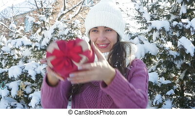 beautiful woman holding a gift box in the form of heart