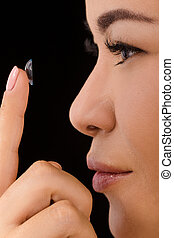 Closeup of woman putting contact lenses