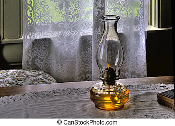 Oil Lamp - A table lamp filled with lamp oil, sits on a...