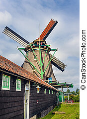 Tall windmill behind single story farmhouse - Tall windmill...