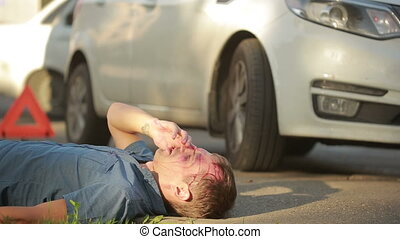 Girl helping injured in a car accident man. pedestrian...