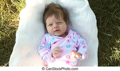 Baby lying on the grass - Little cute baby in pink ensemble...