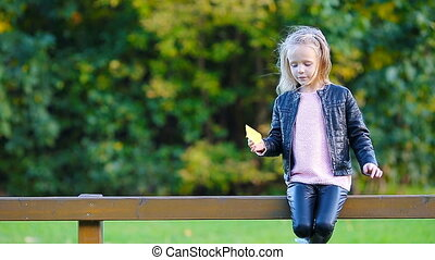 Adorable little girl with yellow maple leaves outdoors at...