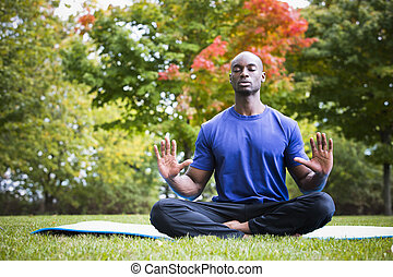 young man exercising yoga - young black man wearing athletic...