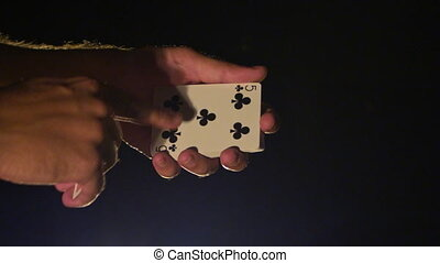Closeup Hands Show Black Clubs Card against Darkness -...