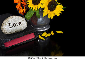 stone on bible with sunflowers