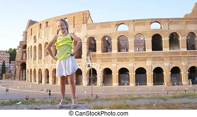 Adorable little active girl having fun in front of Colosseum...