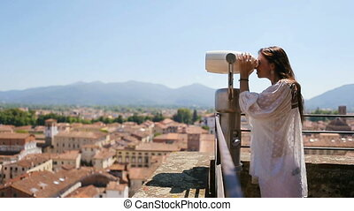 Beautiful girl looking at coin operated binocular on terrace...