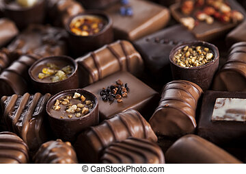 Chocolate bars and pralines on wooden background - Praline...