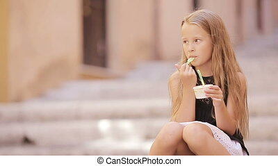 Adorable girl eating ice-cream outdoors at european city....