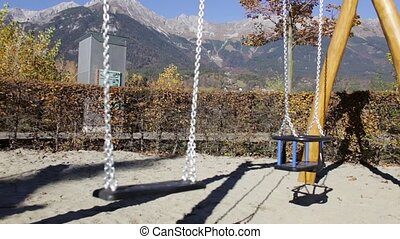 Empty Swing at the Playground - Empty swing moving with the...