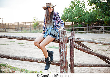 Happy woman cowgirl sitting on fence - Happy cute young...
