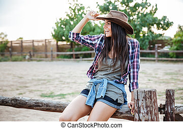 Cheerful relaxed young woman cowgirl sitting on fence and...