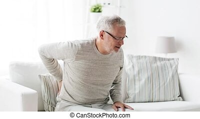 unhappy senior man suffering from backache at home 104 -...