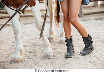 Legs of woman and horse walking together on ranch - Closeup...