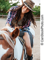 Cheerful woman cowgirl enjoying riding horse in village -...