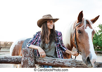 Smilng woman cowgirl standing with her horse on ranch -...