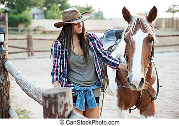 Woman cowgirl walking with her horse on ranch - Beautiful...