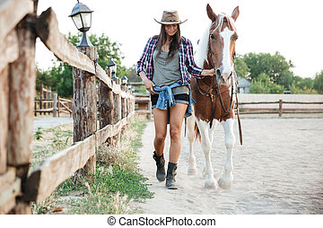 Woman cowgirl in hat walking with her horse in village -...