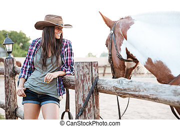 Smilng pretty young cowgirl standing with her horse on ranch...