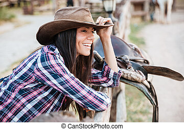 Smiling woman cowgirl leaning on fence in village - Smiling...