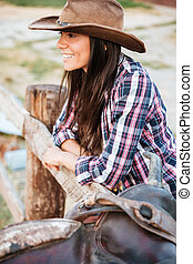 Close up portrait of a smiling cowgirl leaning on fence -...