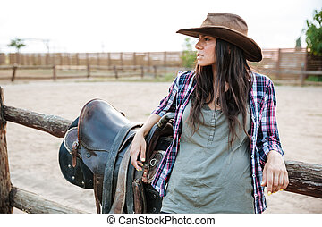 Young cute cowgirl leaning on the ranch fence and looking...