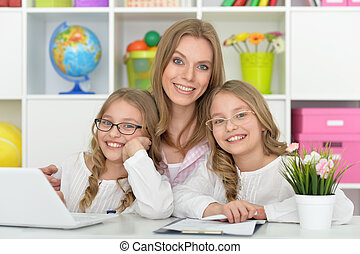 mother helping her daughters with homework - Mother helping...