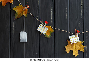 autumn leaves, pills, tea bag on clothespins hanging -...