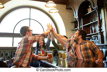 friends with beer making high five at bar or pub - people,...