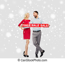 happy couple with red sale sign over snow - people,...