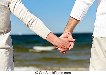 close up of senior couple holding hands on beach - family,...