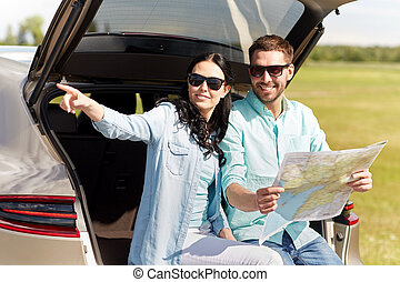 happy man and woman with road map at hatchback car -...