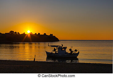 Sunset over the sea and small ship silhouette - Golden...