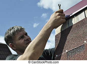 Man is repairing the roof, hammerin