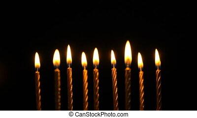 Footage golden burning candles set on black background. 4K...