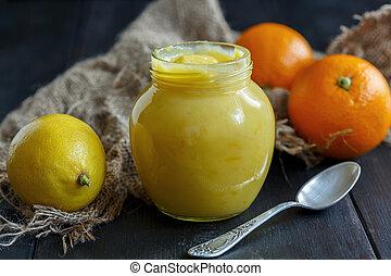 Jar with lemon custard. - Lemon custard and citrus fruits on...